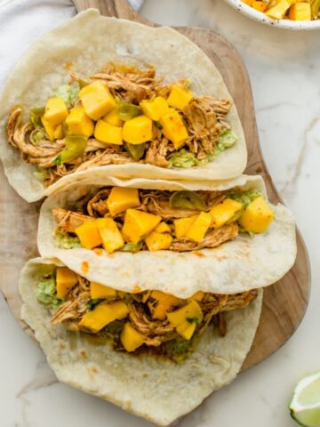 Three chicken tacos with mango salsa on a wood cutting board.