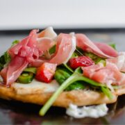 Side view of a mini salad pizza with greens, prosciutto, and asparagus on mozzarella.