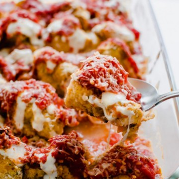 Glass cooking dish with roasted cauliflower topped with tomato sauce and melted mozzarella cheese.