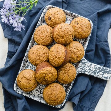 A ceramic blue and white tray filled with raisin bran muffins on a blue dish towel.
