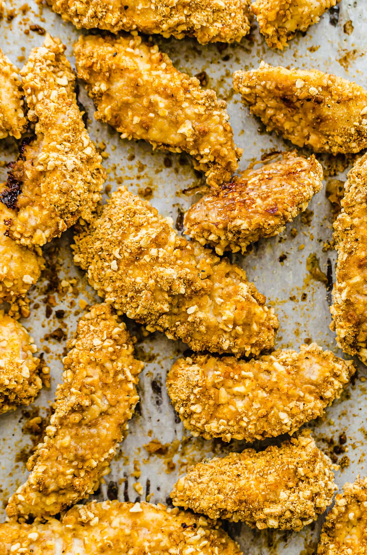 A close up shot of crispy pretzel chicken on a baking sheet.