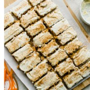 Carrot cake sliced into bars on a parchment paper lined cutting board.