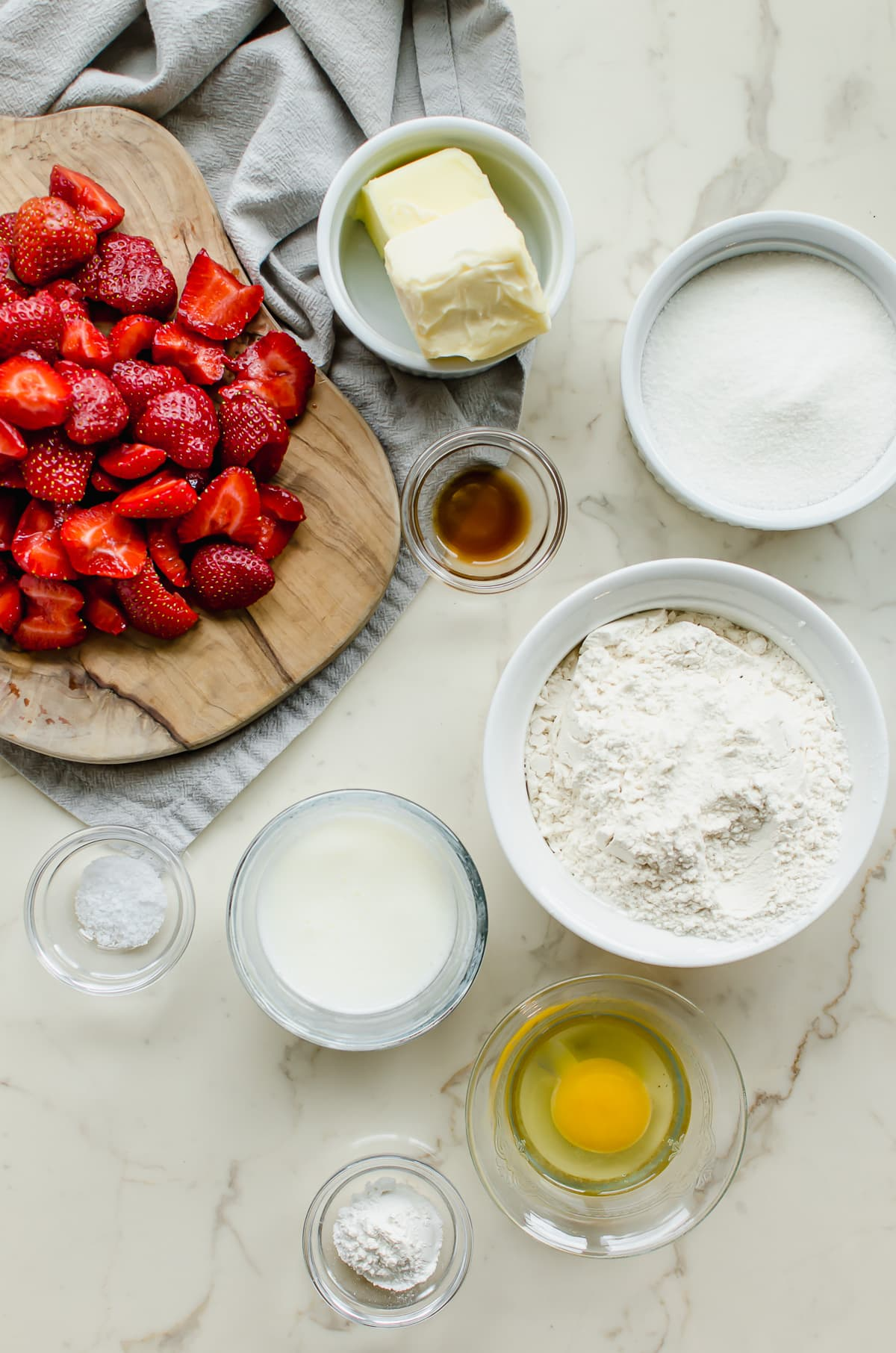 Measured ingredients in white bowls for making a strawberry buttermilk cake.