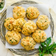 A wire charger lined with parchment with cheddar bay biscuits on top with yellow dish towel and sprigs of fresh parsley.