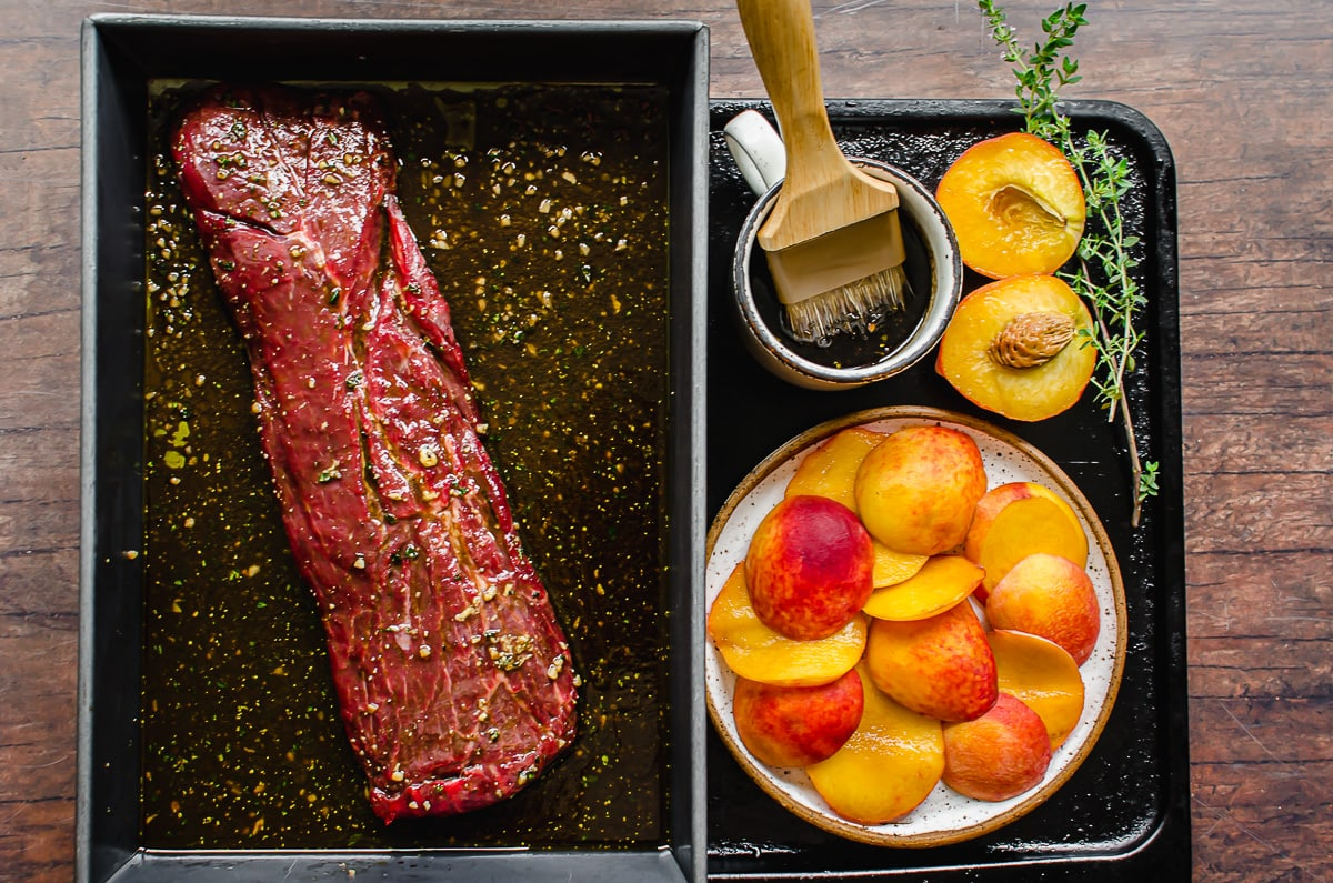 Marinated steak in a pan with a plate of peaches and a cup of basting sauce with a brush.