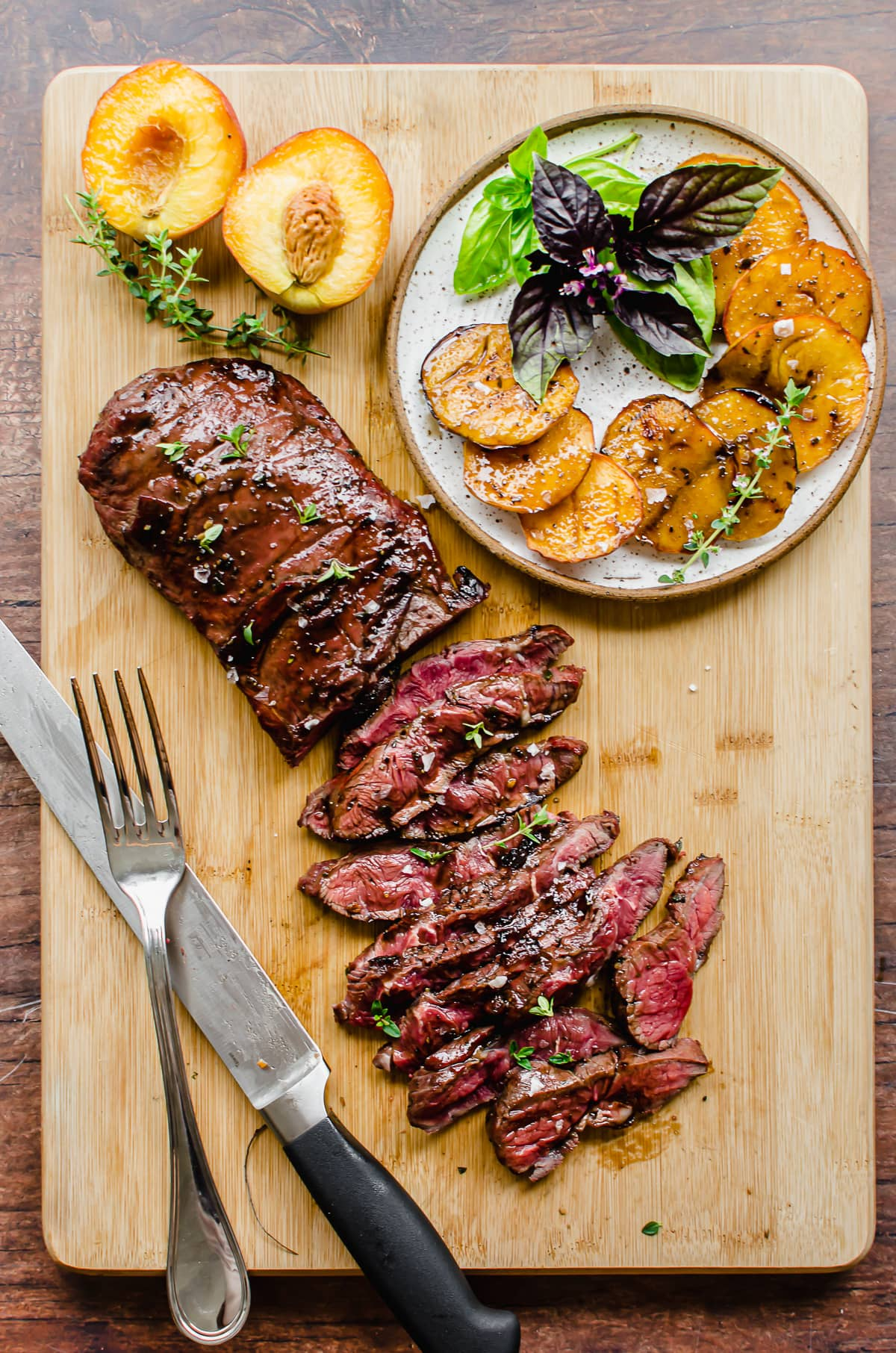 Overhead shot of balsamic steak being sliced on a cutting board with a plate of peaches and basil on the side.