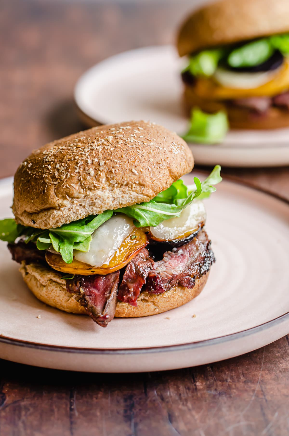 Straight-on shot of a steak sandwich on a wheat bun with lettuce, cheese, and peaches.