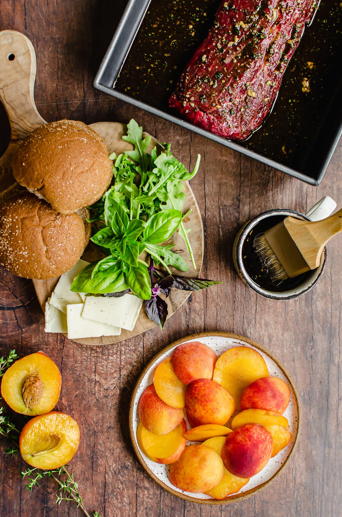Measured ingredients for grilled steak sandwiches with peaches on a wood background.