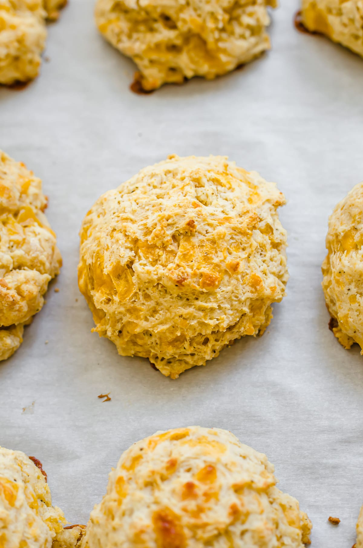 Cheddar bay biscuits on parchment paper.