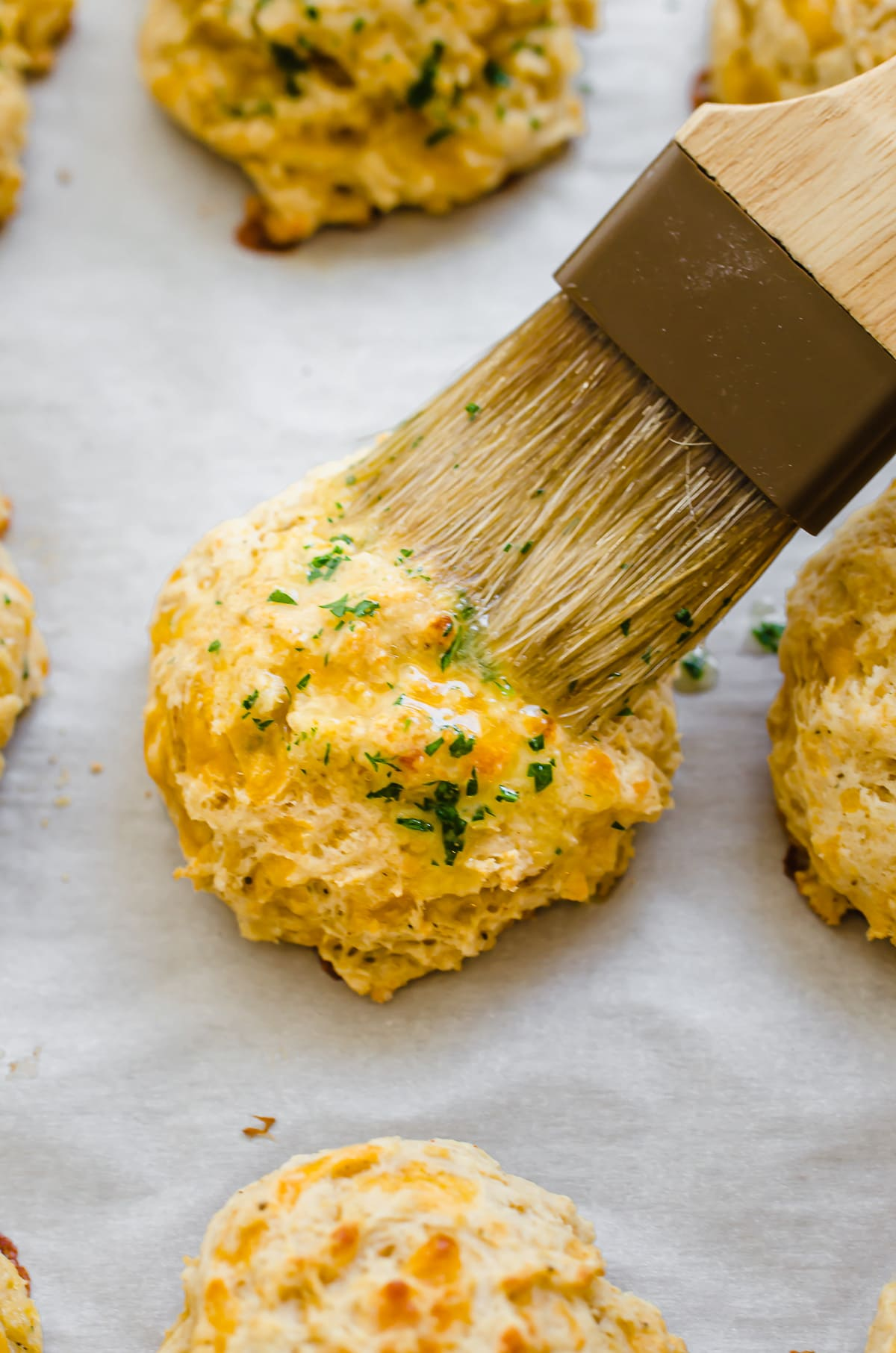 A brush spreading on butter herb topping on a cheddar bay biscuit.
