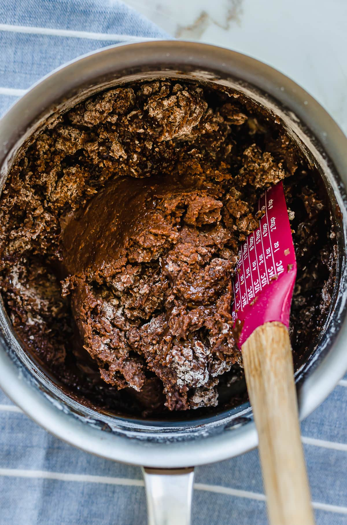 Chocolate cookie batter being mixed with a rubber spatula in a saucepan.