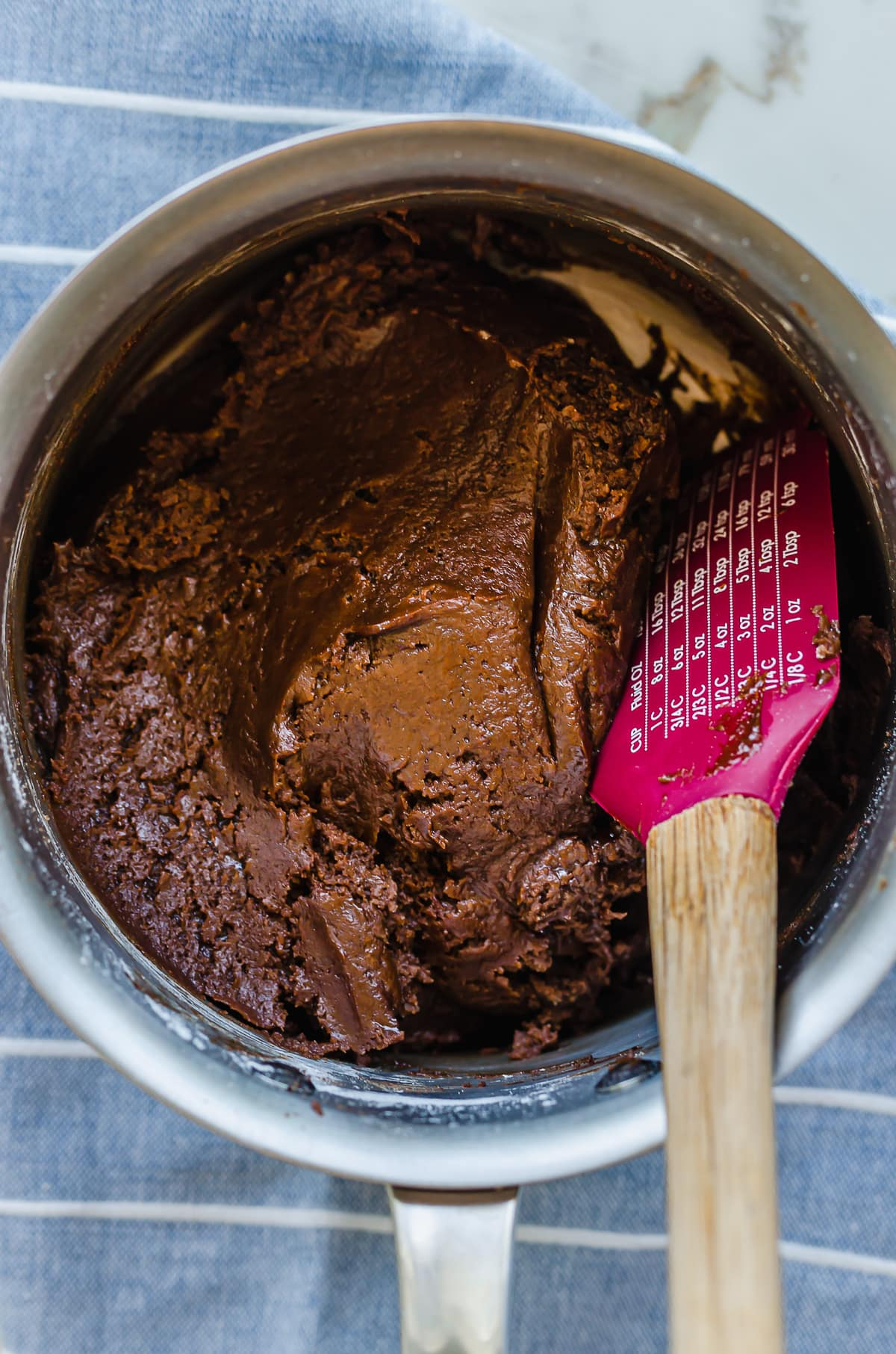 Chocolate tart dough being folded together in a saucepan.