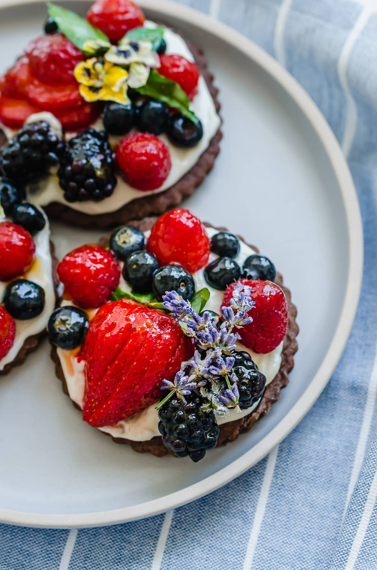 Side shot of a chocolate mini fruit tart on a blue plate.