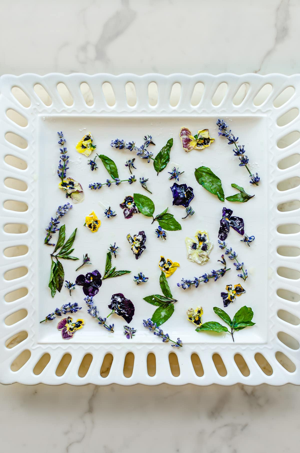 Candied edible mint, lavender, and pansies on a white plate.
