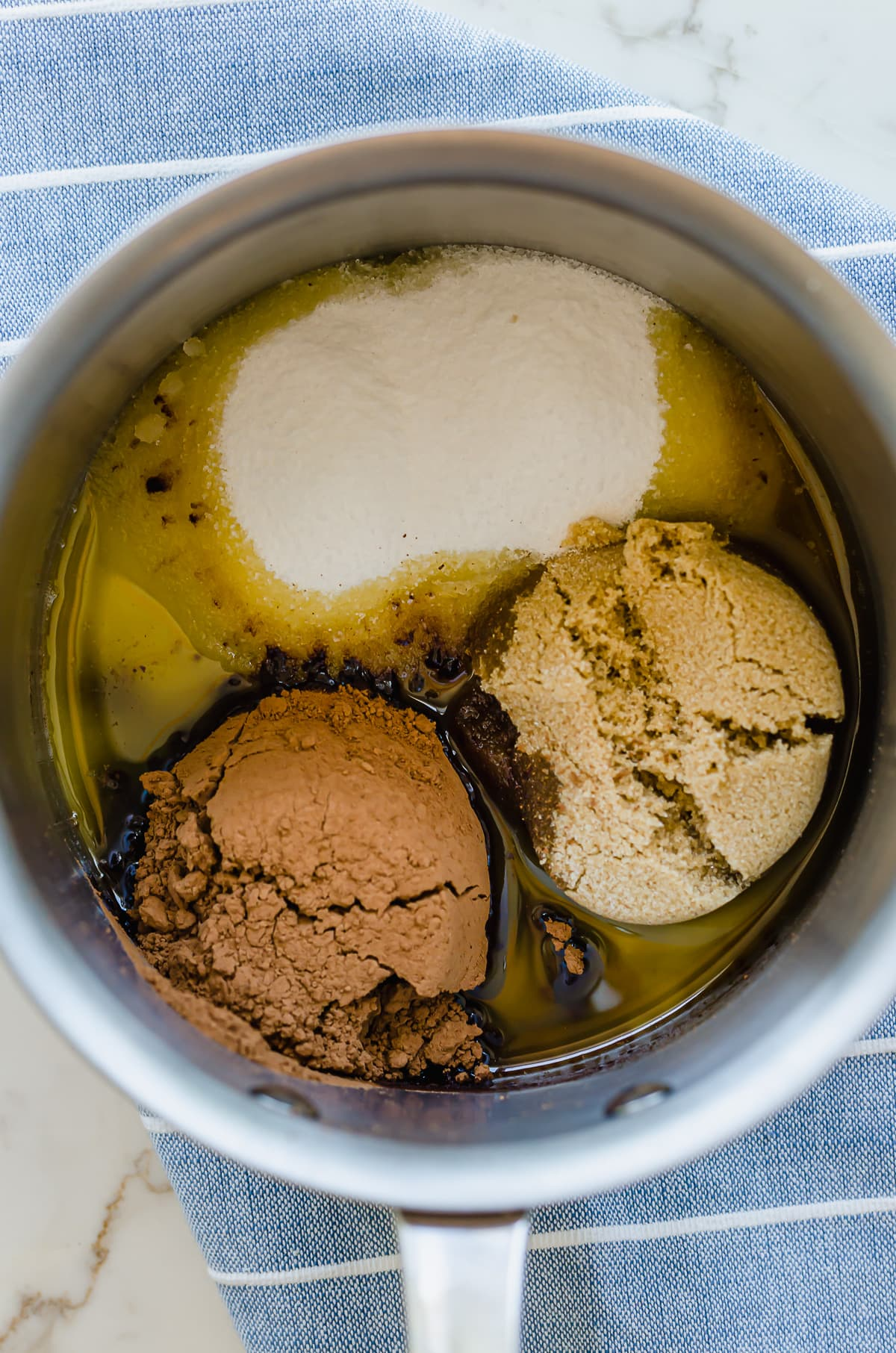 Sugars melting into butter in a saucepan.