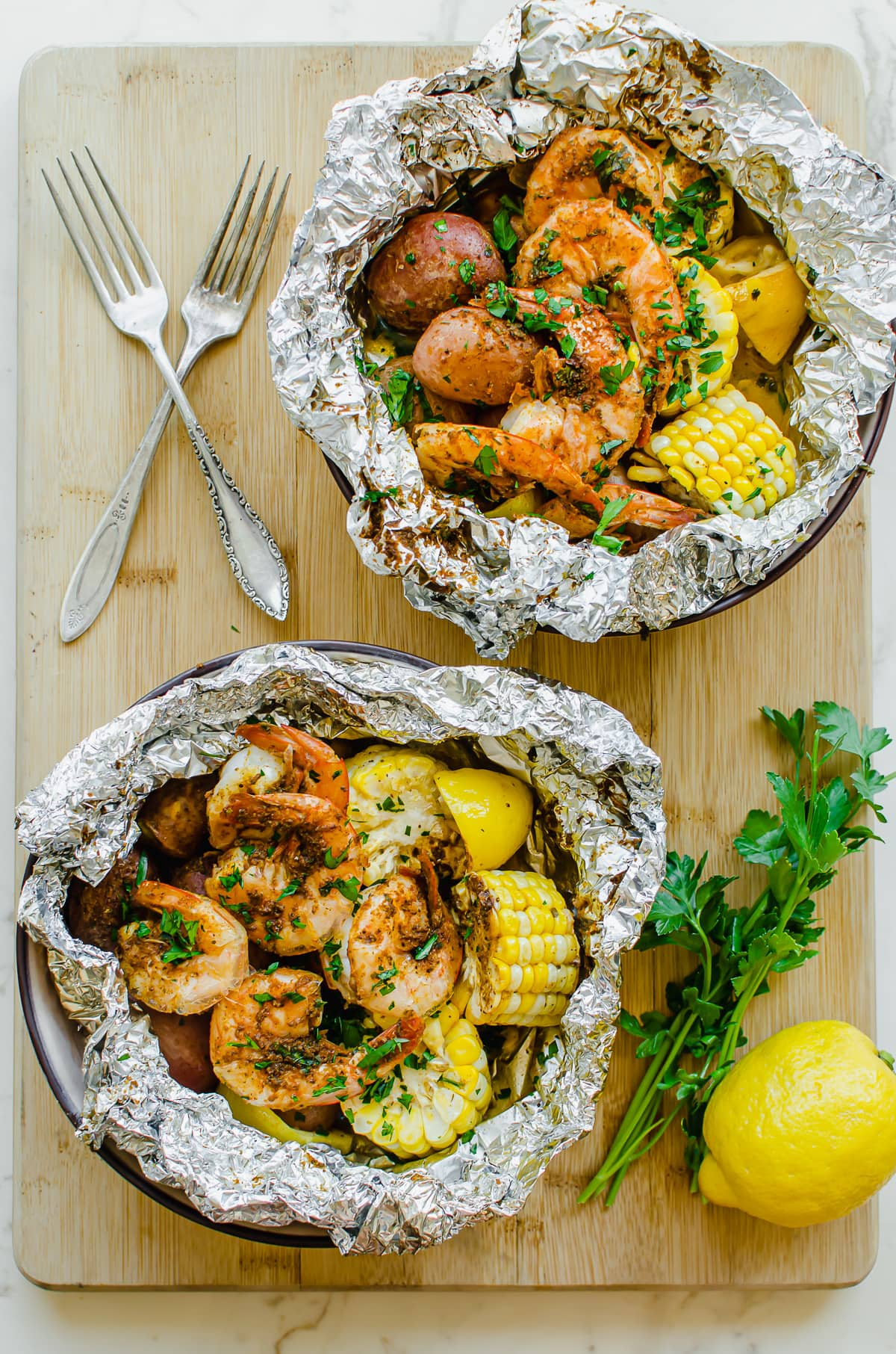 Two bowls of shrimp boil in foil on a wood cutting board with forks on the side.