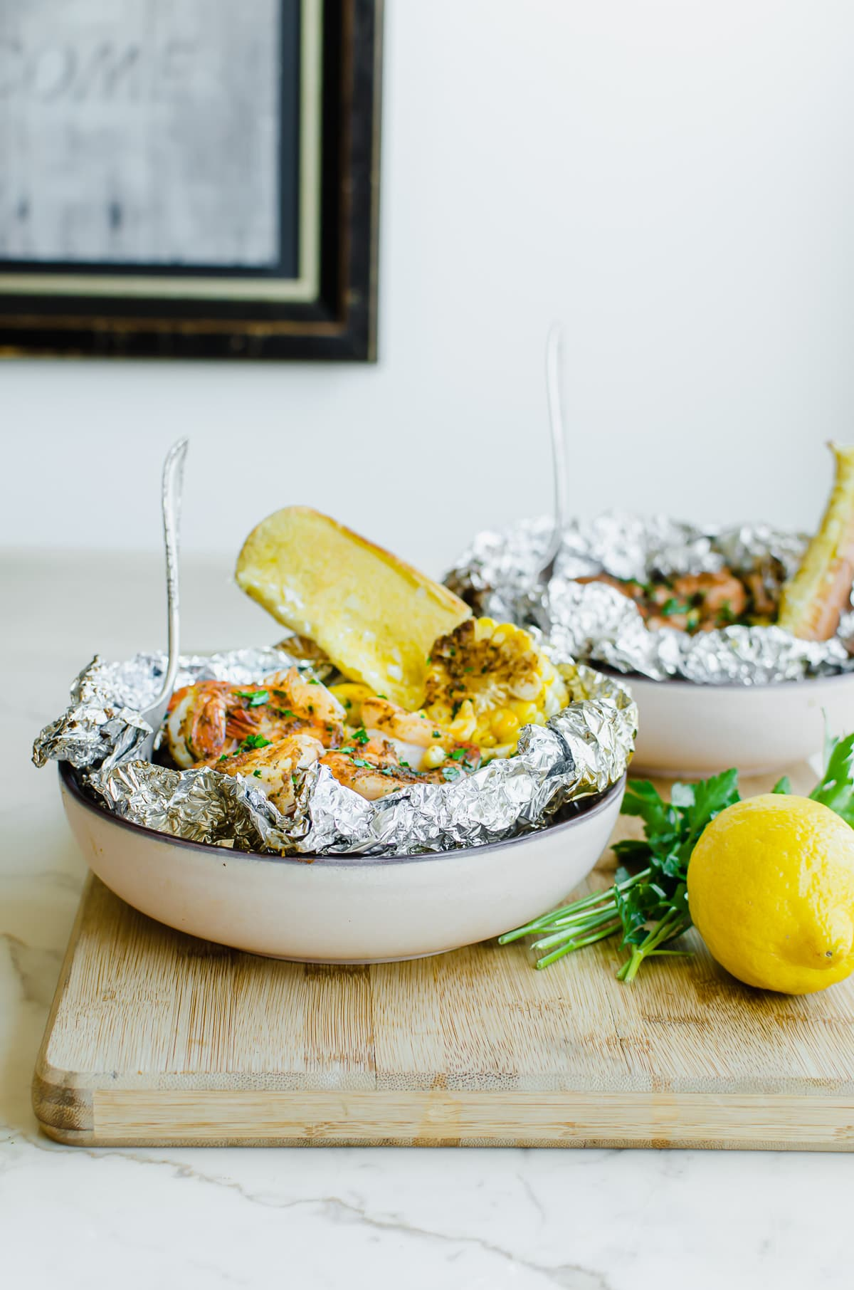 Two bowls of grilled shrimp boil on a wood cutting board with fresh lemon and parsley on the side.