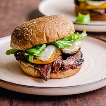 A grilled steak sandwich with peaches on a pink rimmed plate.