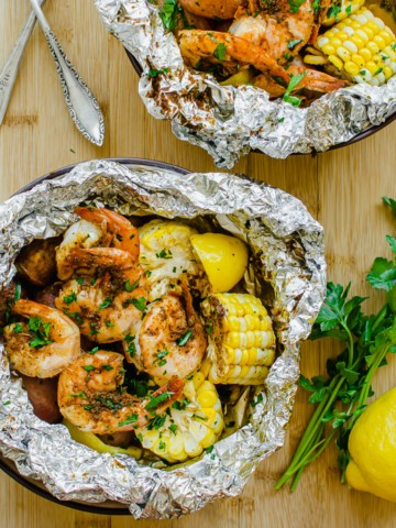Two bowls with foil packs of grilled shrimp, corn, and potatoes.