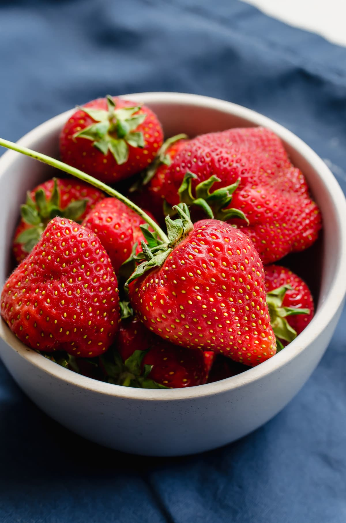 A bowl of fresh strawberries on a blue dish towel.