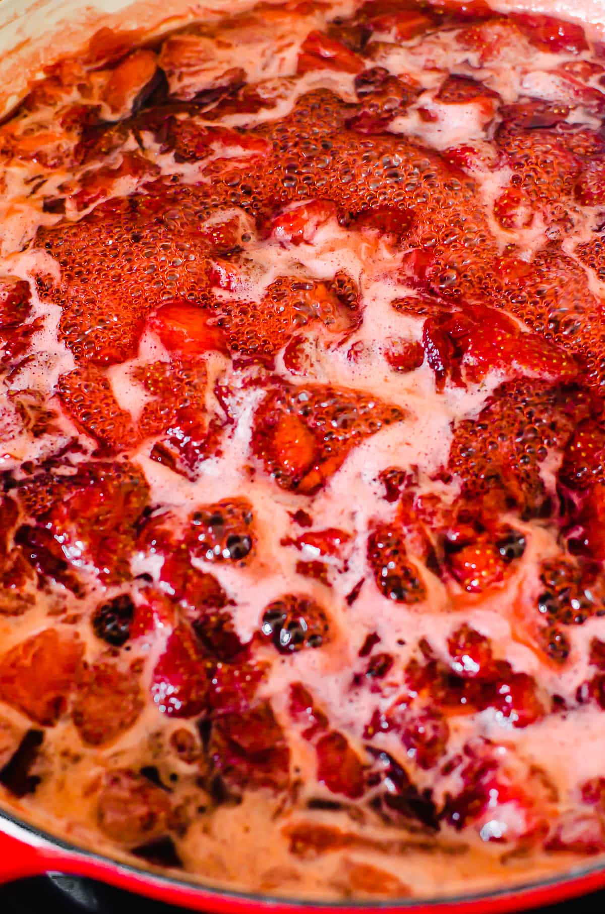 Foam forming on top of a pot of simmering strawberry jam.