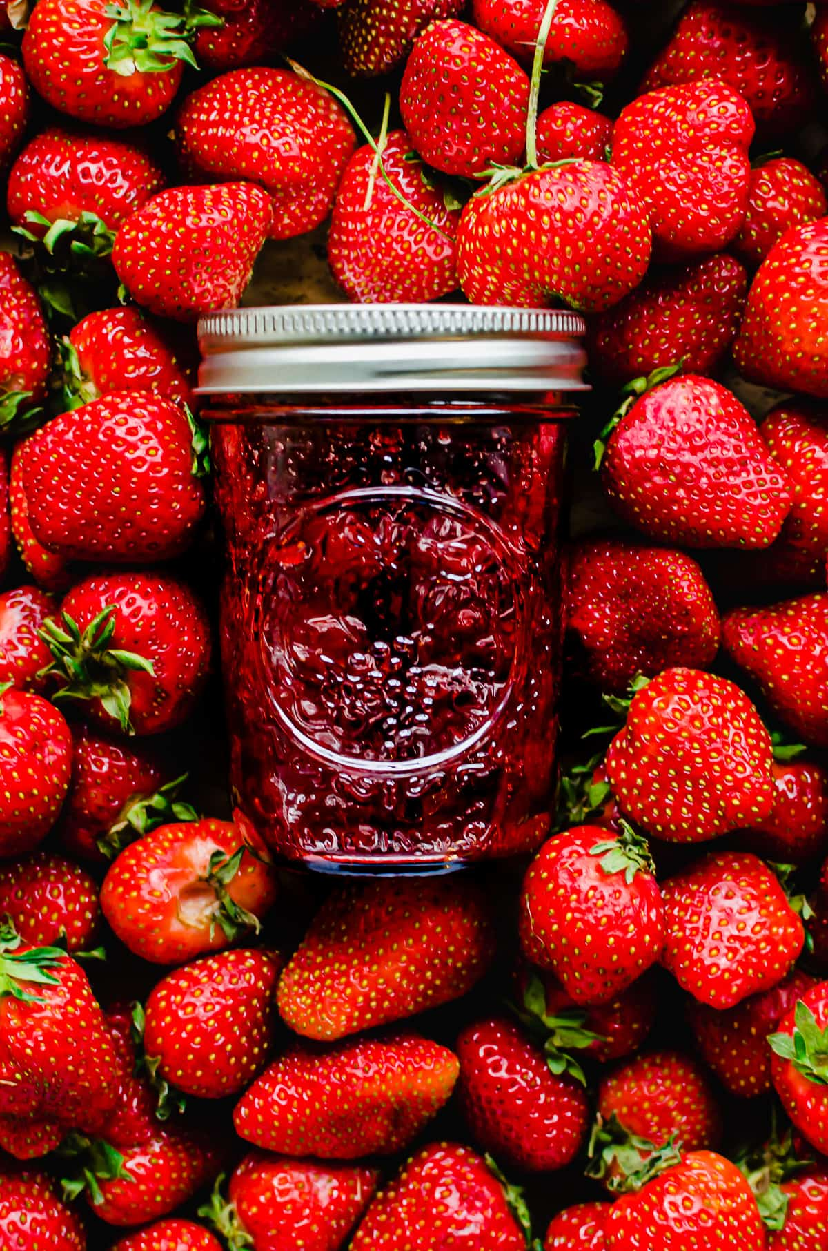 A jar of strawberry jam on top of a bed of fresh strawberries.
