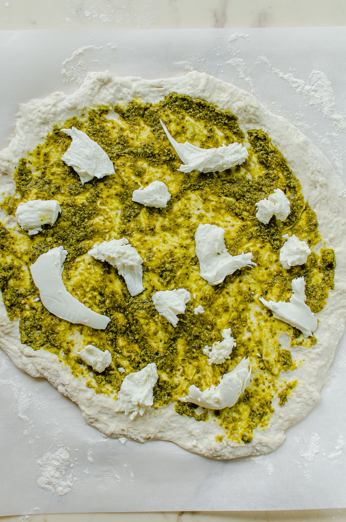 Pizza dough topped with pesto and fresh mozzarella.