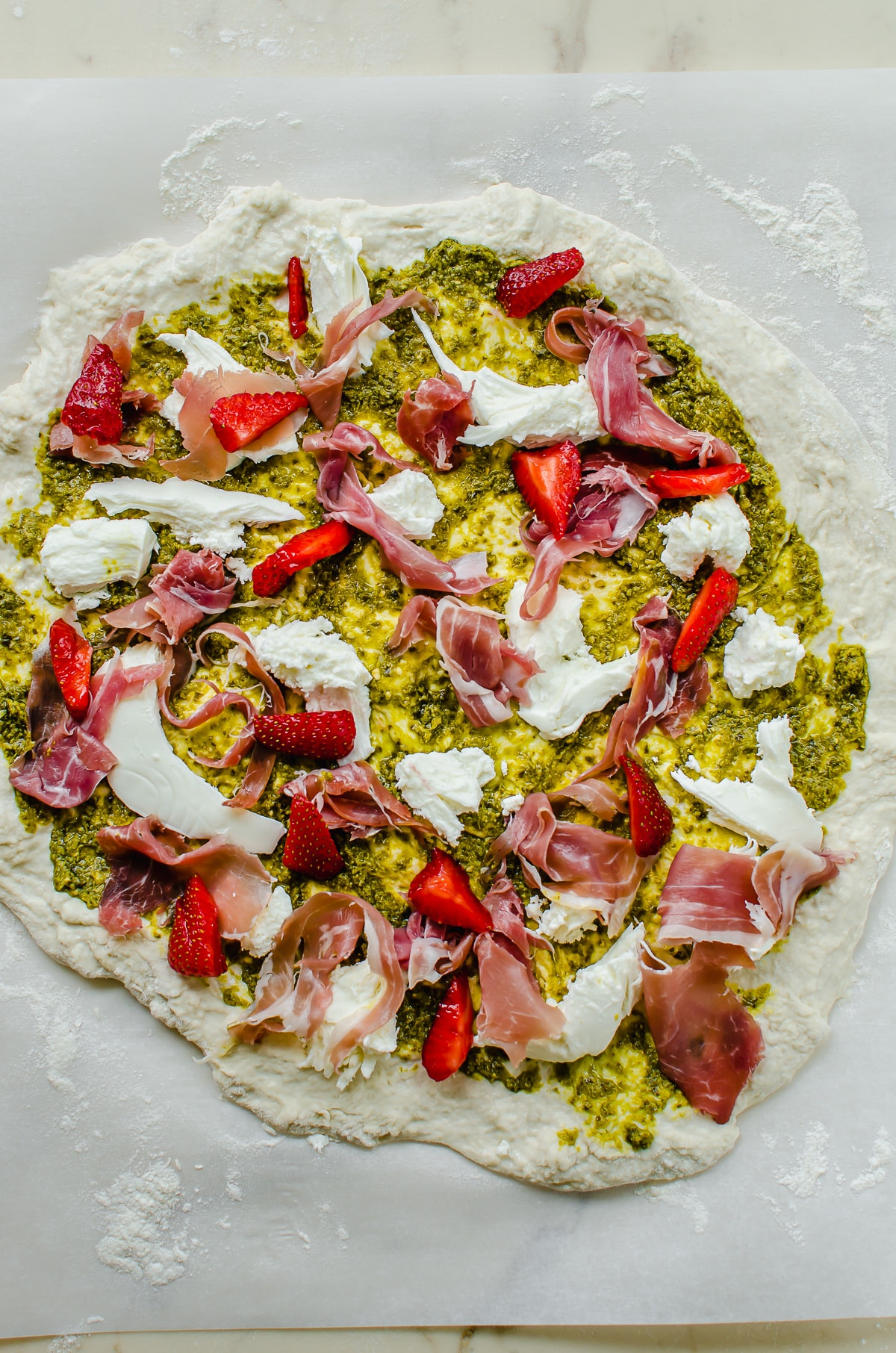 Pizza dough topped with pesto, fresh mozzarella, prosciutto and strawberries.
