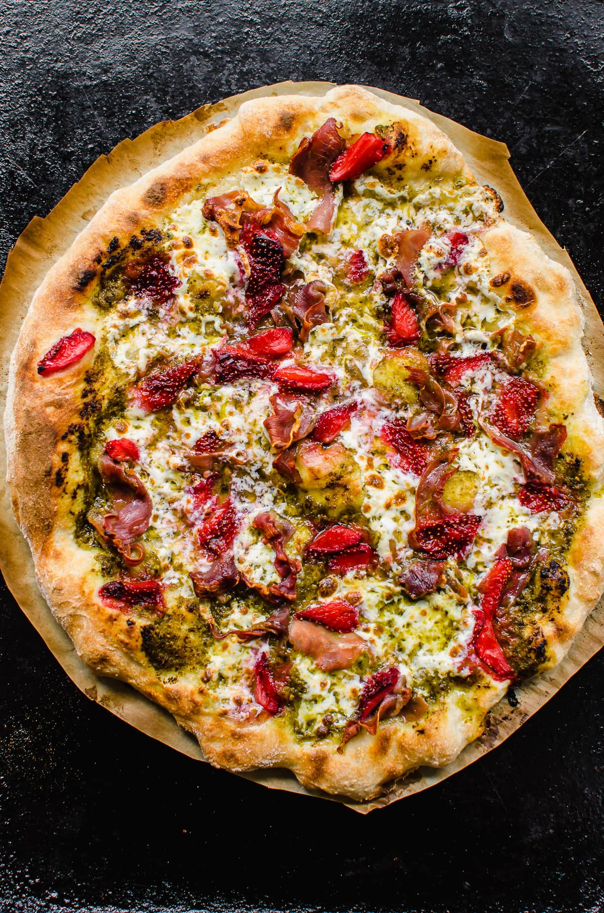 A baked prosciutto pizza with strawberries and pesto.