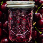 A jar of cherry jam surrounded by a background of cherries.