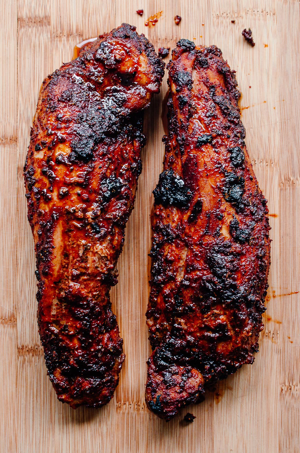 Two whole chile rubbed pork tenderloins on a wood surface.