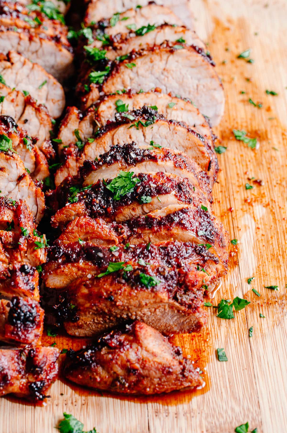 Pork tenderloin sliced on a wood cutting board with juices on the board and fresh cilantro.