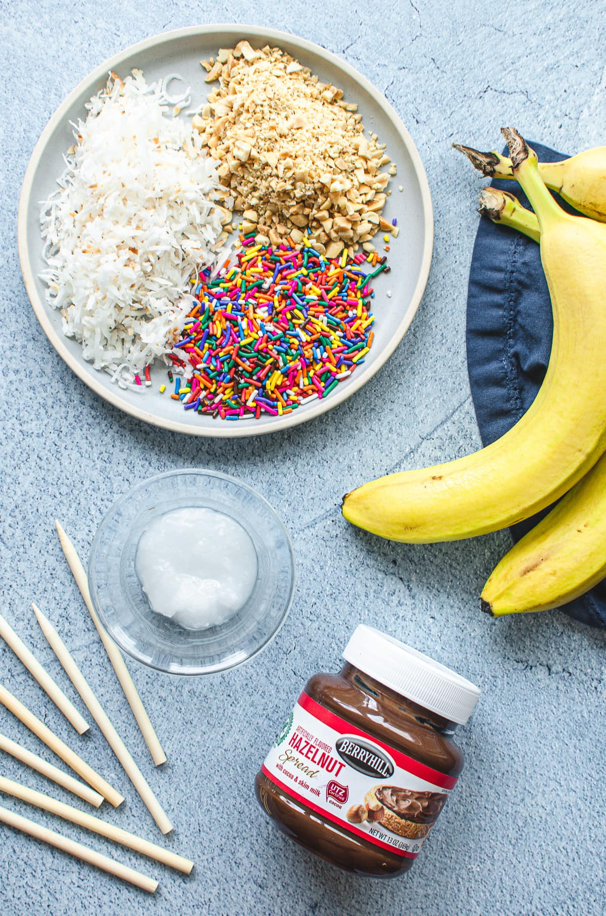 A plate of sprinkles, nuts and coconut flakes with bananas, Nutella, coconut oil, and wooden sticks on the side.