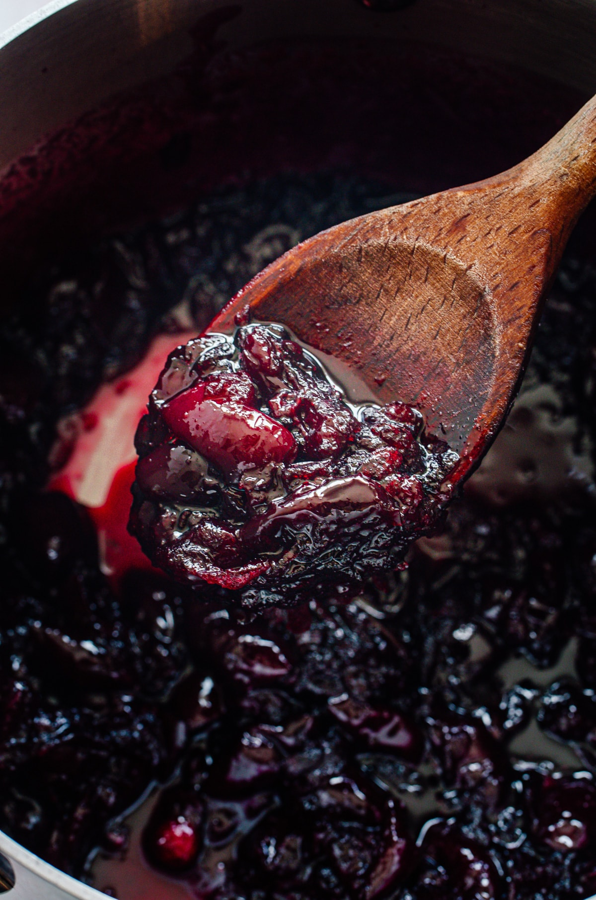 A wooden spoon lifting cherry jam out of a pot of jam.
