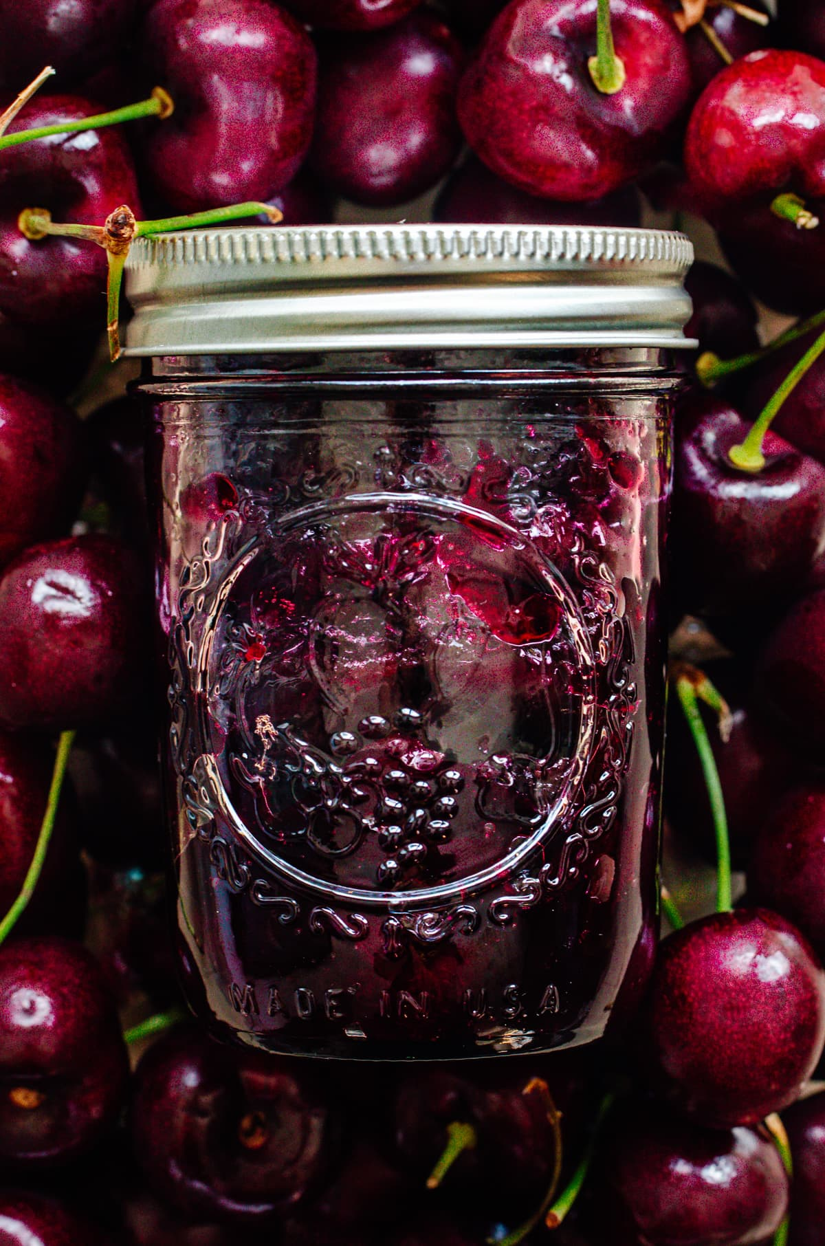A jar of cherry jam surrounded by a background of dark cherries.