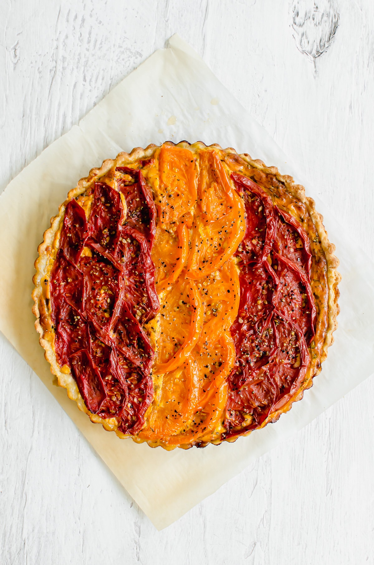 A baked tomato tart on a sheet of parchment paper.