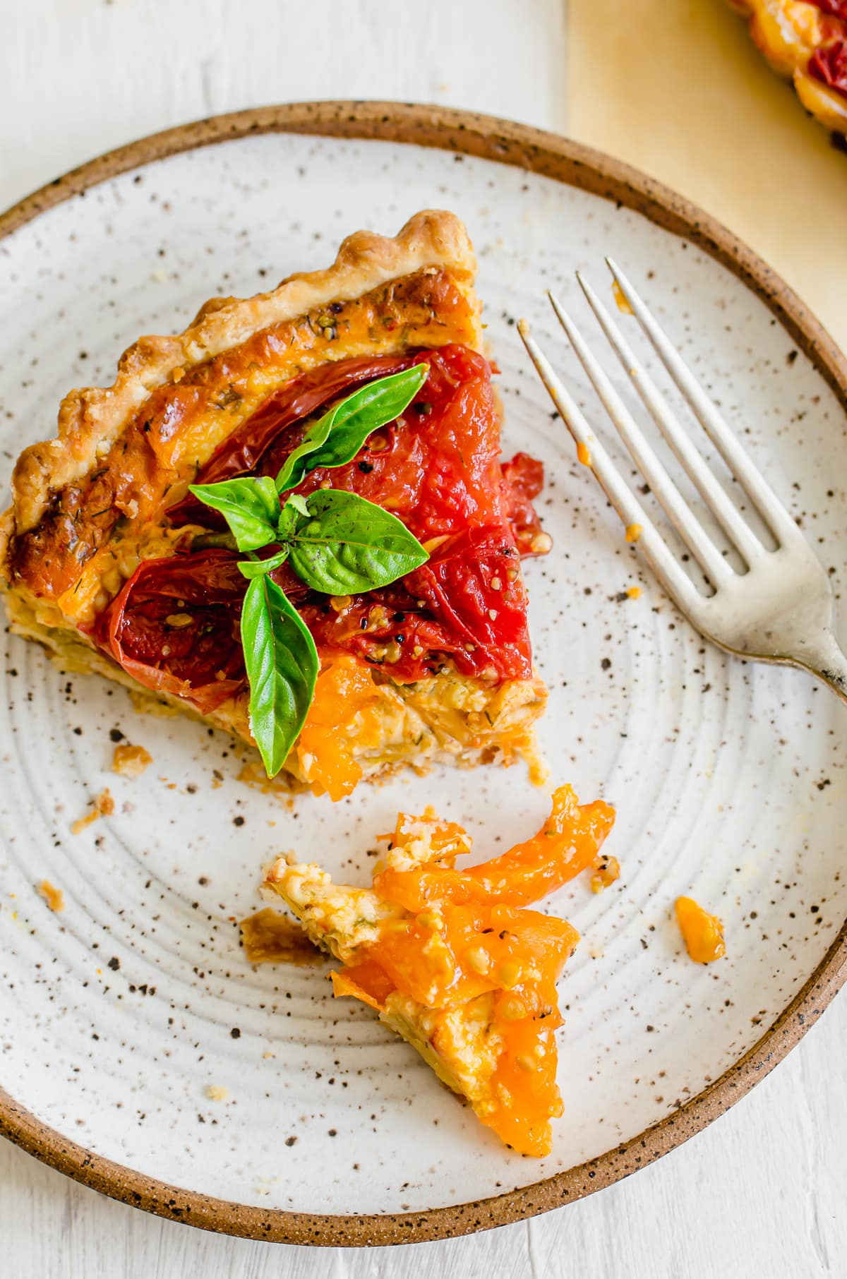 A slice of tomato tart on a plate with a fork and bite cut off.