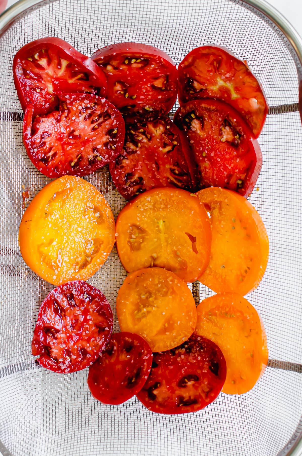 Tomato slices draining in a wire mesh colander.