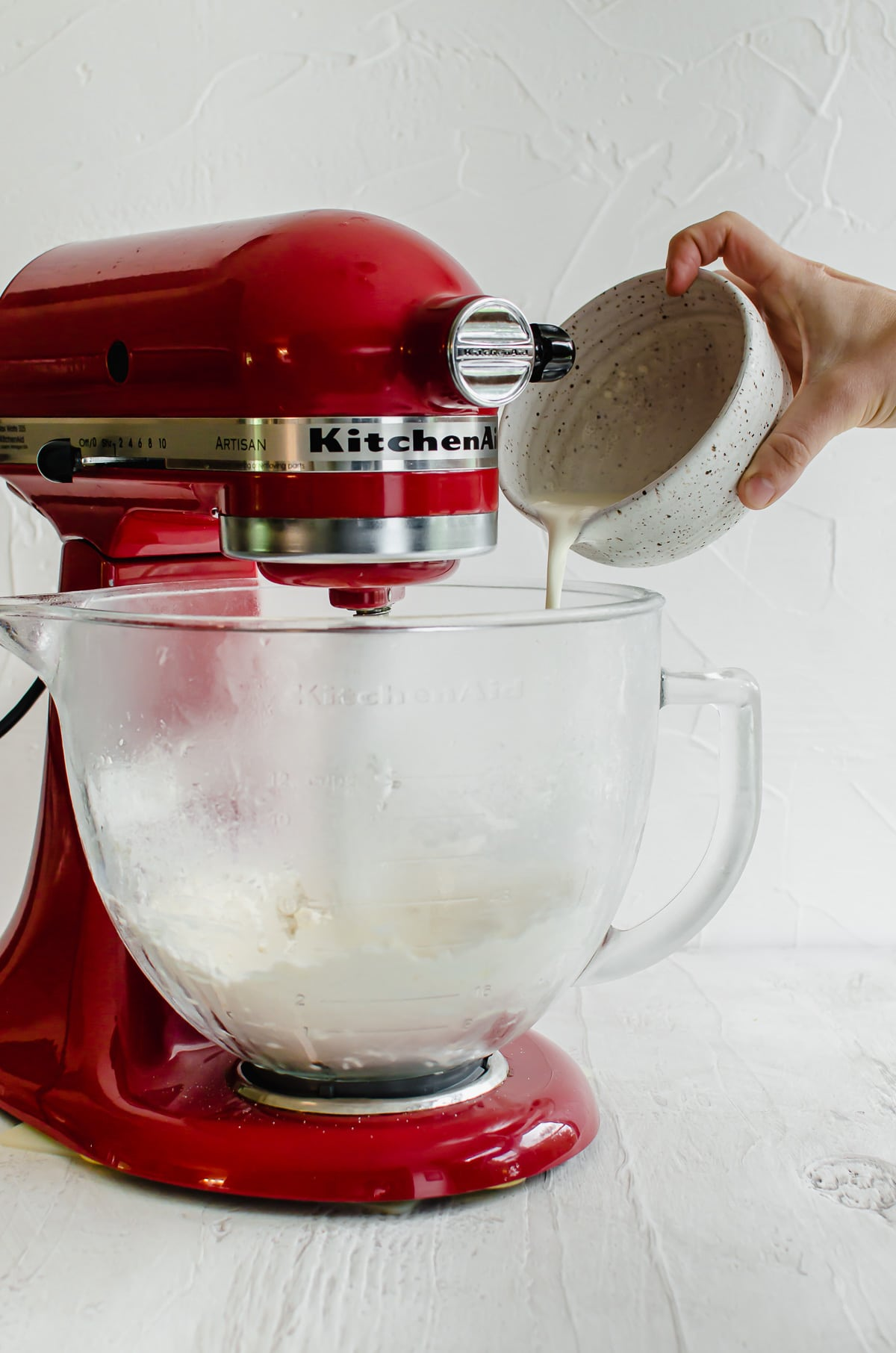 A hand pouring cream into a stand mixer bowl with dough inside.