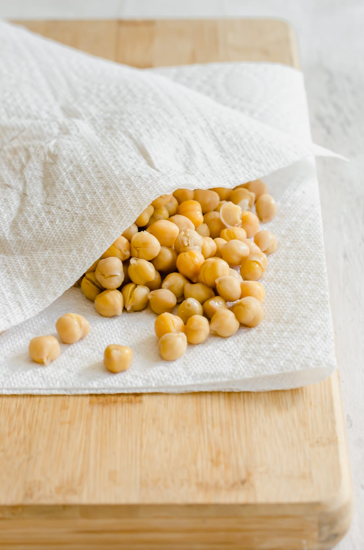 Chickpeas being dried between layers of paper towels on a wood cutting board.