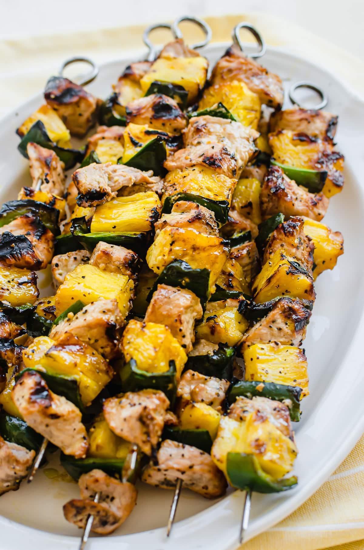 A side shot of pork pineapple kabobs on skewers.