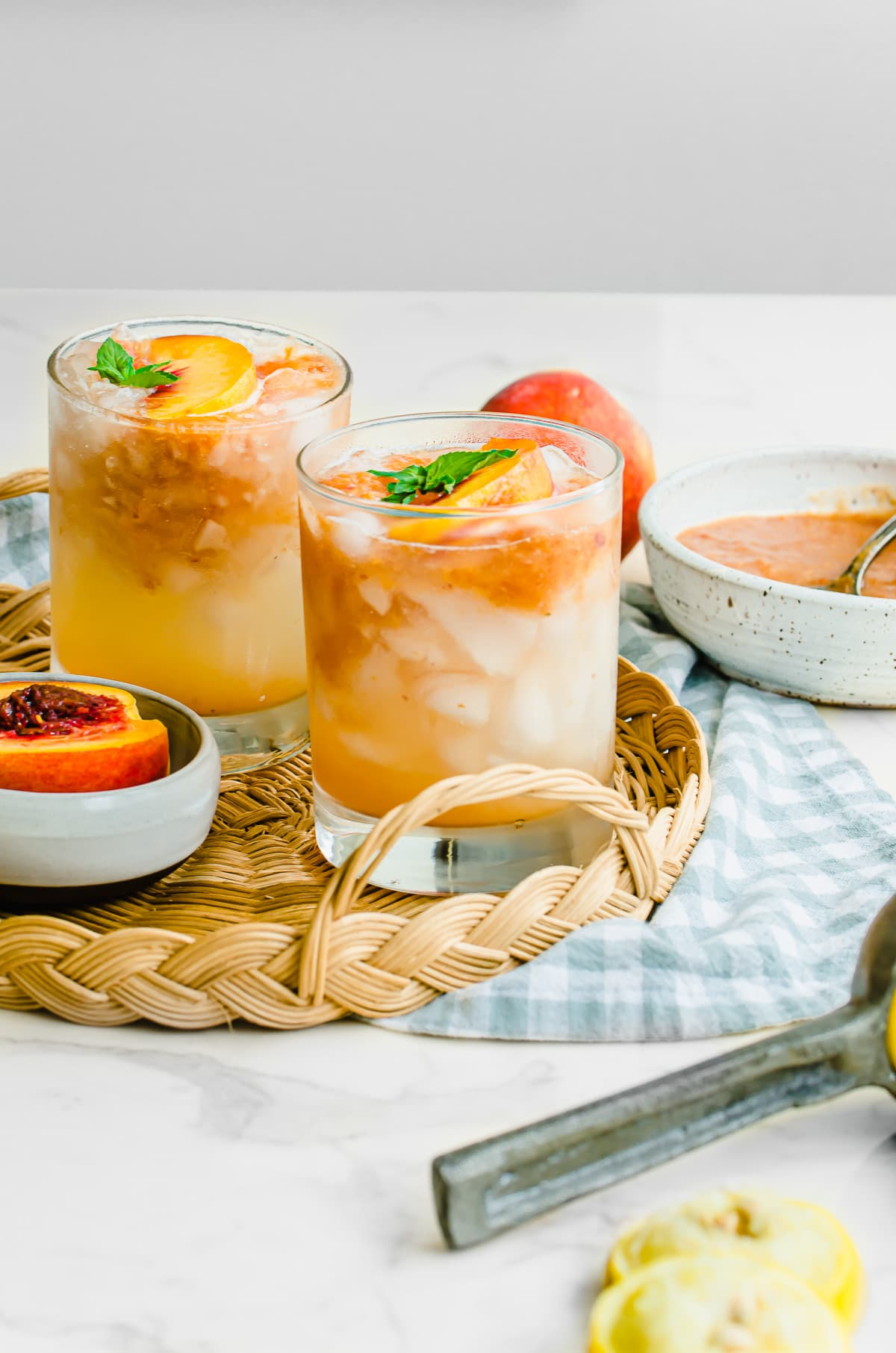 Two glasses of peach lemonade on a wicker serving tray with a gingham dish towel.