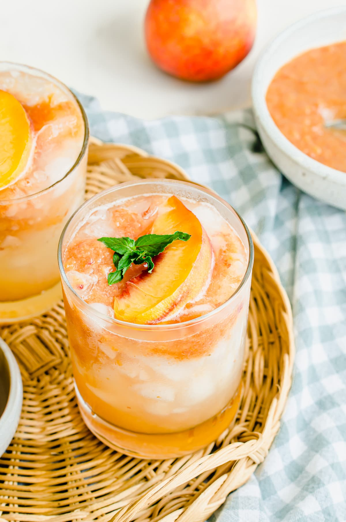 Two glasses of lemonade garnished with peaches on a wicker serving tray and a bowl of peach puree on the side.