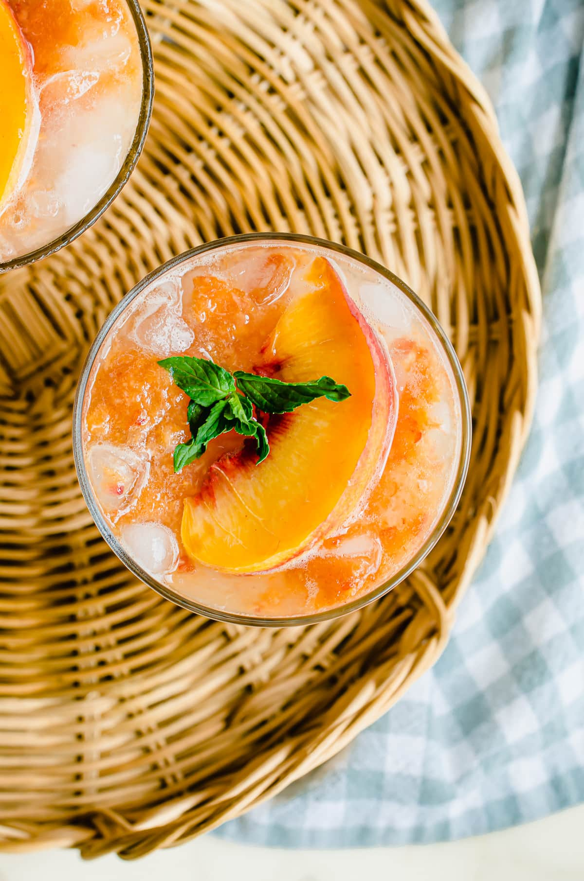 An overhead, close-up shot of a glass of lemonade garnished with a peach and mint sprig.