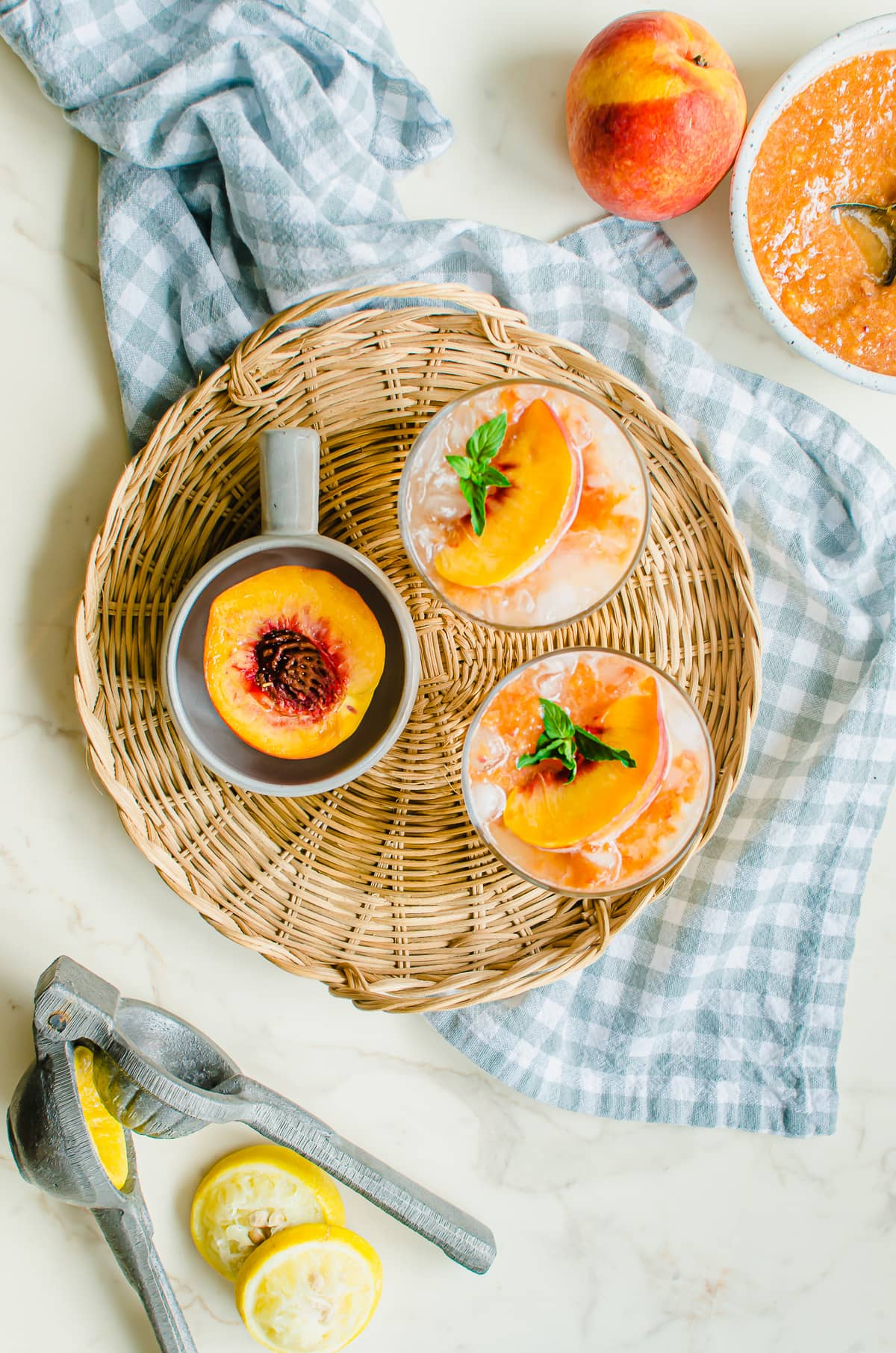 Overhead shot of styled glasses of lemonade with peaches and lemons on the side.
