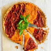 A tomato tart on parchment paper topped with basil sprigs and two slices of tart coming out on the side.