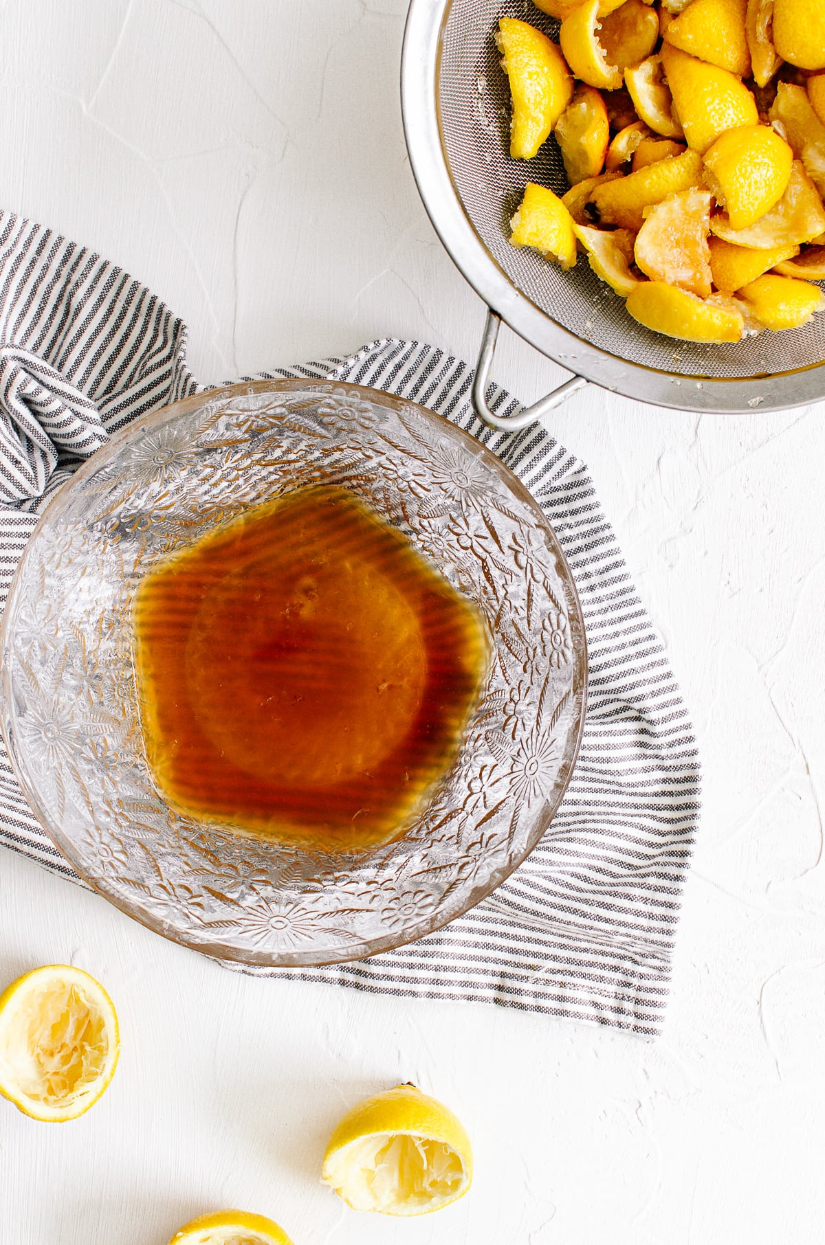 A bowl of lemon syrup with a mesh strainer of lemon rinds on the side.