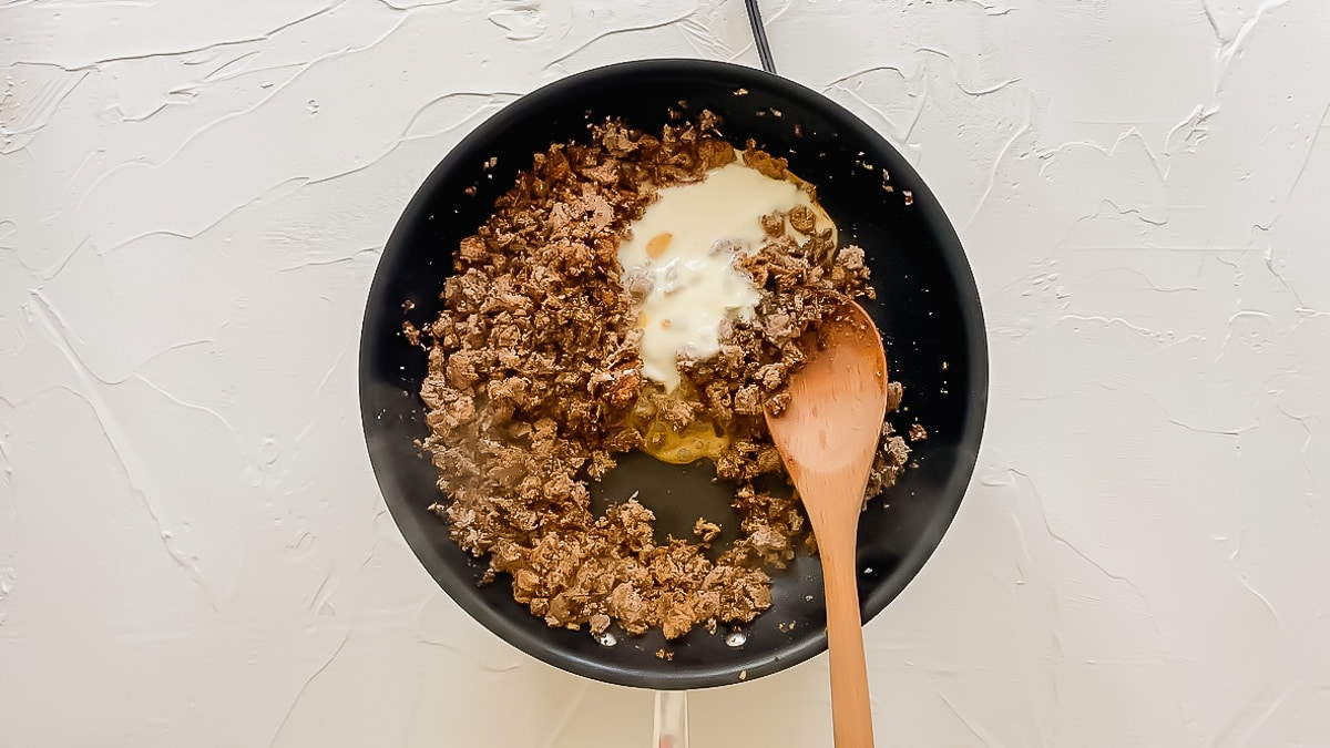 White queso being stirred into ground beef in a skillet.