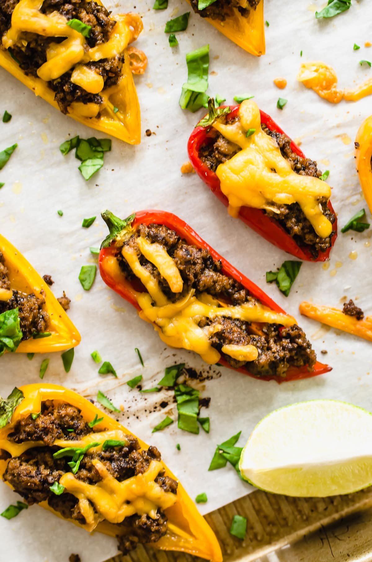 A close up shot of a bell pepper nacho on a parchment lined baking sheet.