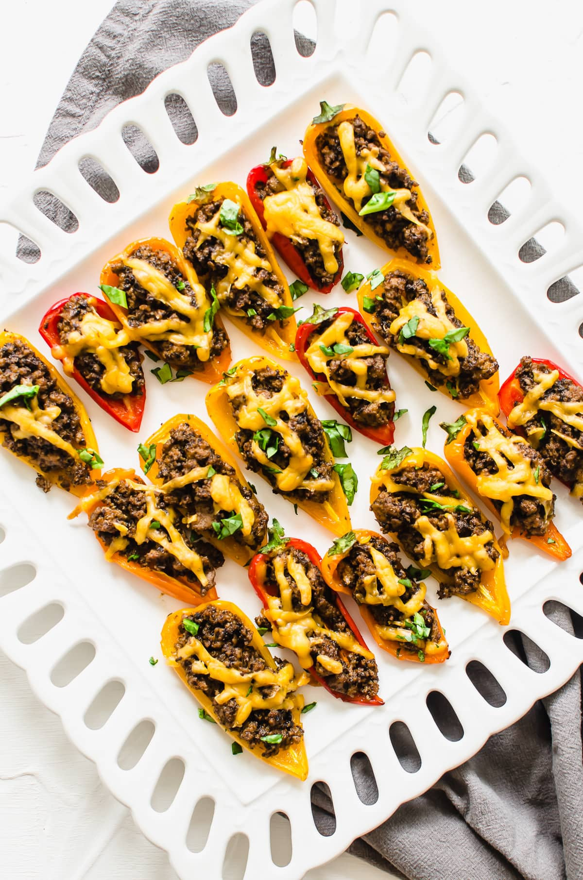 A white platter with bell pepper nachos garnished with chopped cilantro.